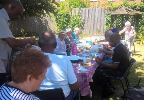 Retirement residents from Matthew Court enjoy a garden party meal