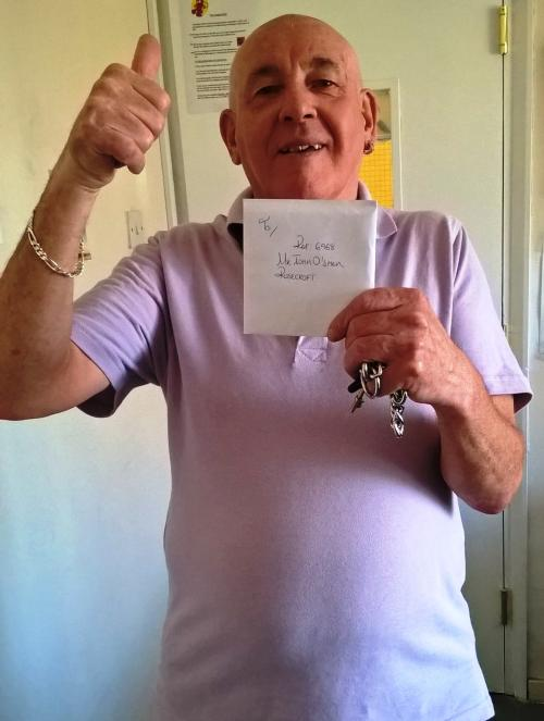 Resident holding his voucher he won for completing survey