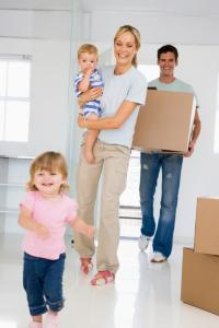 family holding boxed moving in home